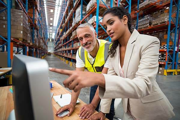 woman-in-suit-pointing-to-computer-in-discussion-with-man-in-warehouse